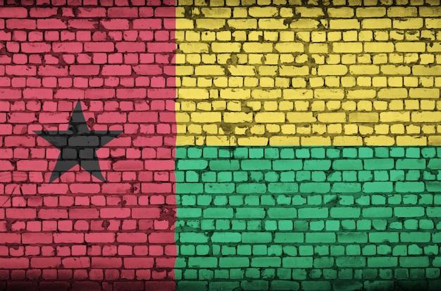 A bandeira da guiné-bissau é pintada em uma parede de tijolos antigos