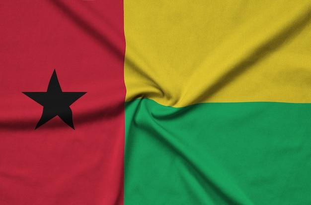 A bandeira da guiné-bissau é retratada em um tecido esportivo com muitas dobras.