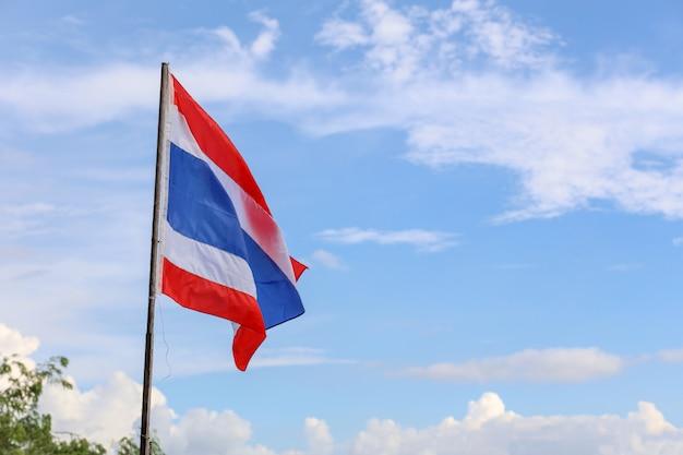 A bandeira da tailândia no mastro de madeira tem o fundo do céu