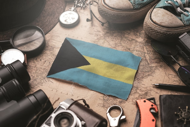 A bandeira das bahamas entre os acessórios do viajante no antigo mapa vintage. conceito de destino turístico.