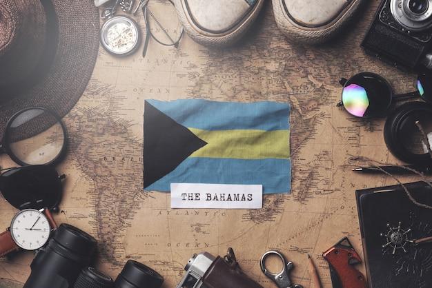 A bandeira das bahamas entre os acessórios do viajante no antigo mapa vintage. tiro aéreo