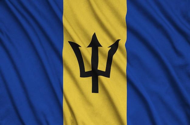 A bandeira de barbados é retratada em um tecido esportivo com muitas dobras.