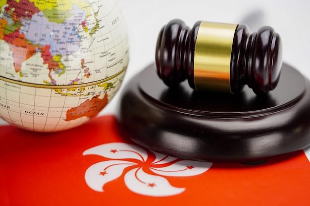 A bandeira de hong kong e o juiz martelam com o mapa do mundo do globo. conceito de tribunal lei e justiça.