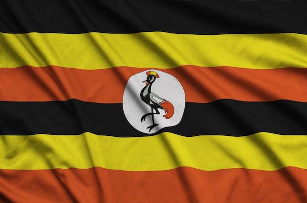 A bandeira de uganda é retratada em um tecido esportivo com muitas dobras.
