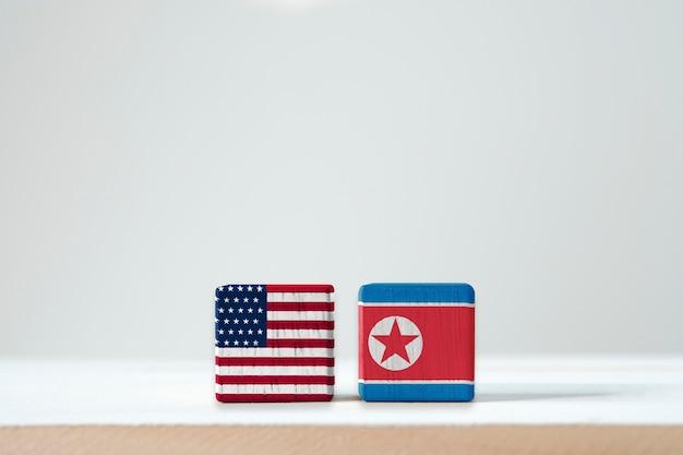 A bandeira dos eua e a bandeira da coreia do norte imprimem a tela em cúbico de madeira. é conflito para ambos os países em armas nucleares militar e sanção econômica