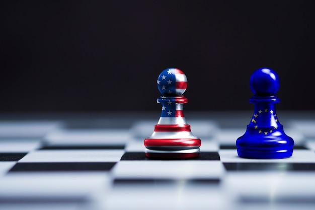 A bandeira dos eua e a bandeira da ue imprimem a tela no xadrez de dois peões para a batalha. é símbolo do aumento da barreira tributária tarifária dos estados unidos da américa para produtos de importação de países da ue