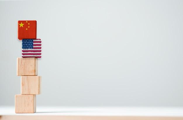 A bandeira dos eua e a bandeira de china imprimem a tela no cúbico de madeira. é símbolo da barreira do imposto da guerra do comércio da tarifa entre os estados unidos da américa e a china