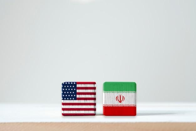 A bandeira dos eua e a bandeira de irã imprimem a tela em cúbico de madeira. é símbolo do estado unido de américa e irã tem o conflito em armas nucleares e o estreito de hormuz.