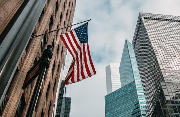 A bandeira dos eua ou estados unidos da américa em um mastro de bandeira perto de arranha-céus sob um céu nublado