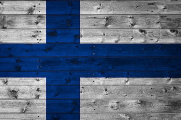 A bandeira nacional da finlândia é pintada em um campo de tábuas fixadas com um prego.