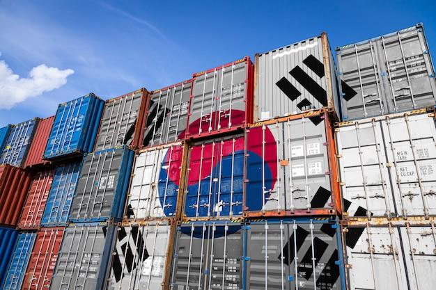A bandeira nacional de south koreon grande número de contêineres de metal para armazenar mercadorias empilhadas em fileiras umas sobre as outras.