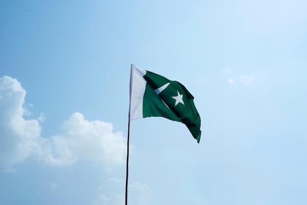 A bandeira nacional do paquistão voando no céu azul com nuvens