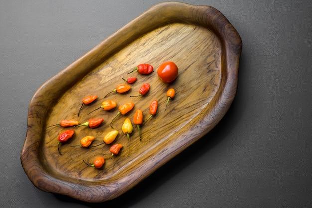 A bandeja de madeira contém pimentões vermelhos que perseguem um tomate.