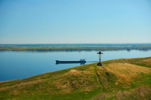 A barcaça vazia perto da costa no fundo do mar azul e céu.