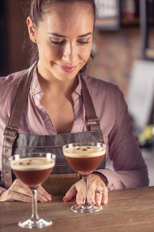 A barmaid serve dois coquetéis de café expresso martini em um bar.