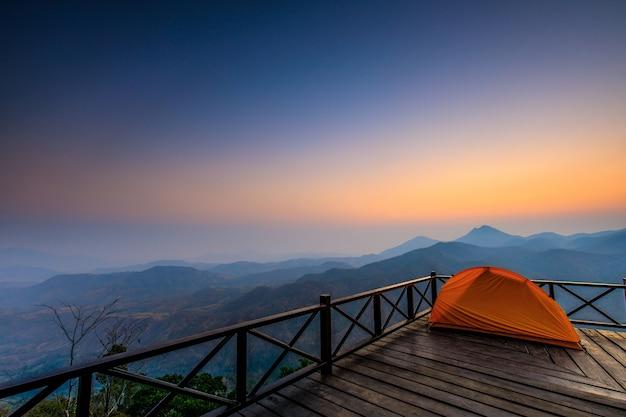 A barraca do caminhante alaranjado no terraço de madeira na montanha alta.