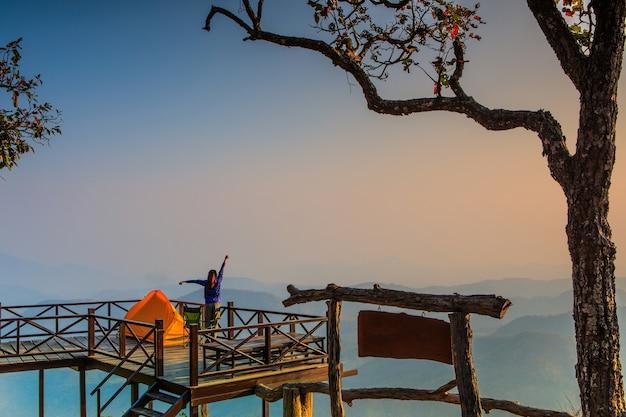 A barraca e o turista alaranjados no terraço de madeira na montanha alta.