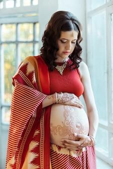 A barriga da mulher grávida com tatuagem de henna