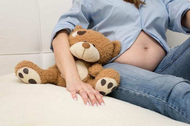 A barriga de uma mulher grávida sentada no sofá. fechar-se.