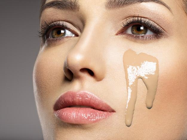 A base de maquiagem cosmética líquida está no rosto feminino. conceito de tratamento de beleza. garota faz maquiagem.