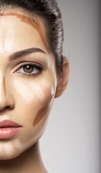 A base tonal da maquiagem cosmética está no rosto da mulher. conceito de tratamento de beleza. garota faz maquiagem.