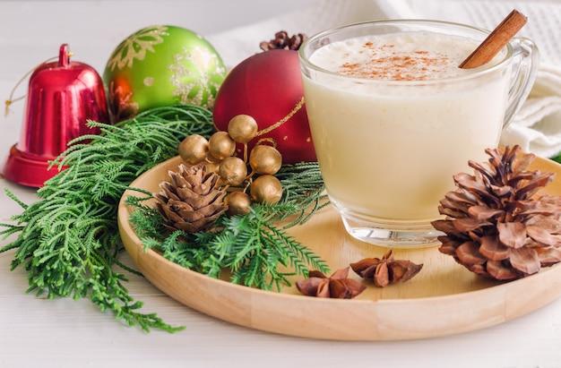 A bebida da gemada para a celebração do natal cobriu com noz moscada à terra e vara de canela.