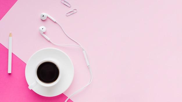 A bebida do café e os fones de ouvido copiam o espaço