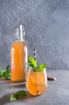 A bebida saboroso saudável caseiro de kombucha na garrafa e no vidro com limão decora a hortelã.