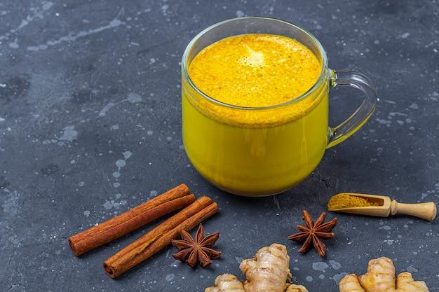 A bebida tradicional indiana de leite de cúrcuma é leite dourado em caneca de vidro com cúrcuma e gengibre raiz