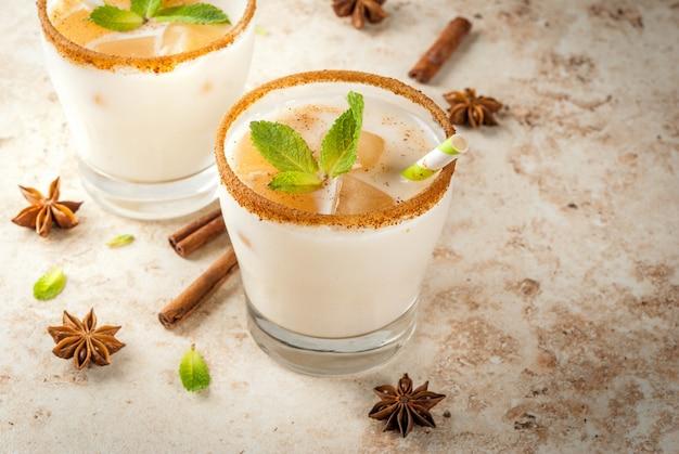 A bebida tradicional indiana é chá gelado ou chai masala, com cubos de gelo de folhas de chai, leite e hortelã. com canudos listrados. na mesa de pedra bege clara. copie o espaço