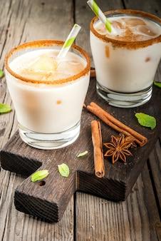 A bebida tradicional indiana é chá gelado ou chai masala, com cubos de gelo de folhas de chai, leite e hortelã. com canudos listrados, sobre uma tábua de madeira. em uma velha mesa de madeira rústica. copie o espaço