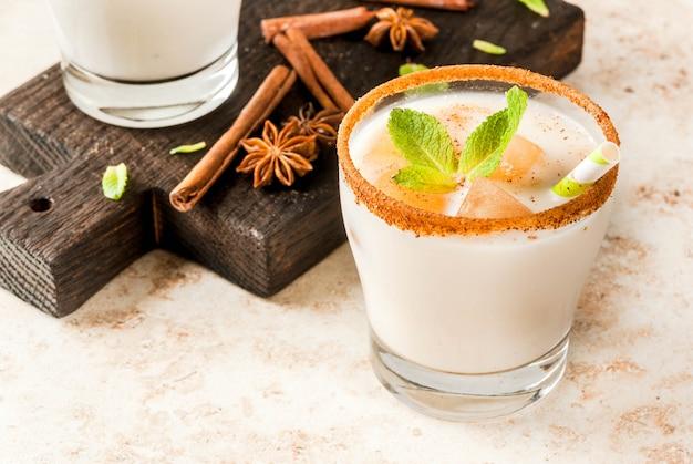 A bebida tradicional indiana é chá gelado ou chai masala, com cubos de gelo de folhas de chai, leite e hortelã. com canudos listrados, sobre uma tábua de madeira. na mesa de pedra bege clara. copyspace