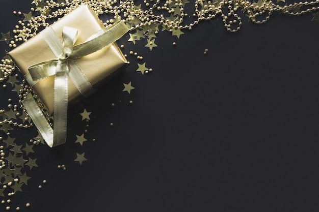 A beira da caixa de presente dourada luxuosa no fundo preto do presente de natal do plano coloca a vista superior. natal.