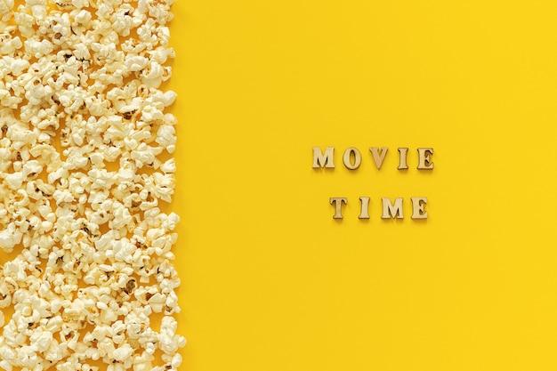 A beira dispersada da pipoca saiu da borda e o tempo do filme no fundo de papel amarelo.