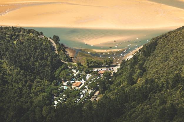 À beira do rio urdaibai cercada por uma floresta verde e uma pequena área de camping em bizkaia, país basco.