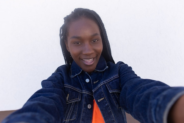 A bela afro-americana feliz tirando uma selfie