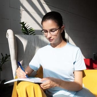 A bela aluna escreve com uma caneta uma tarefa em um caderno enquanto está sentada em uma poltrona em um café
