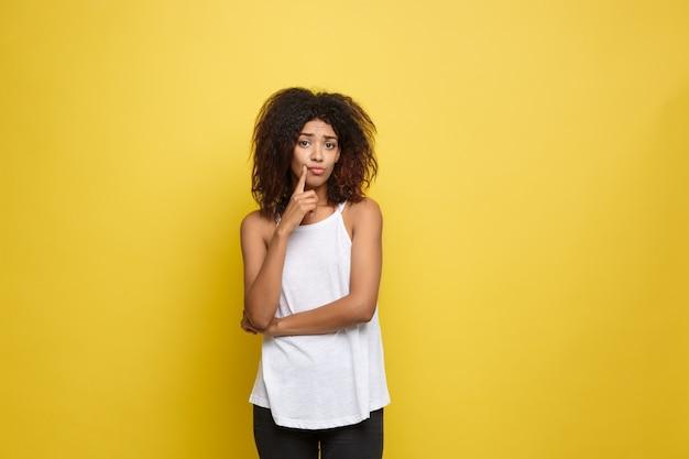 A bela e atrativa mulher afro-americana que publica joga com seus cabelos afro encaracolados. fundo de estúdio amarelo. espaço de cópia.