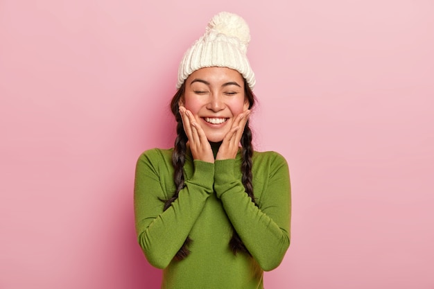 A bela e jovem modelo feminina sente prazer, toca as bochechas com as palmas das mãos, usa um chapéu branco quente de inverno e uma blusa de gola alta casual verde, tem um sorriso largo e brilhante, posa sobre a parede rosa