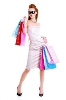 A bela elegante mulher europeia elegante com compras em mãos depois de uma campanha nas lojas.
