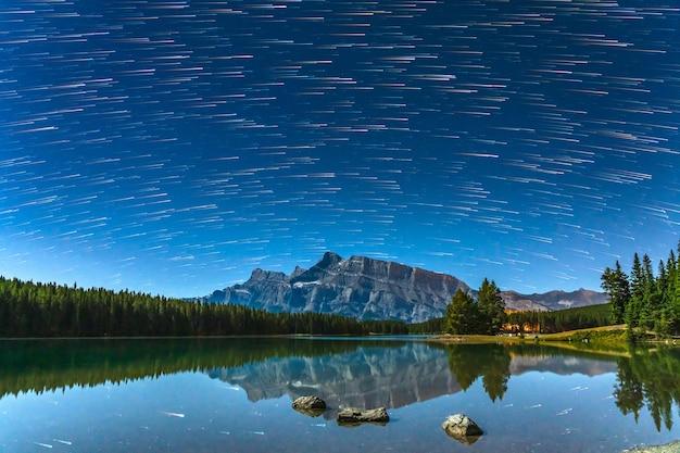 A bela estrela se arrasta acima do monte rundle do lago two jack à noite. parque nacional de banff, canadian rockies, alberta, canadá.