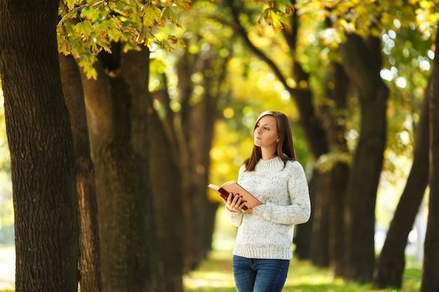 A bela feliz sorridente mulher de cabelos castanhos no suéter branco em pé com um livro vermelho no outono parque da cidade em um dia quente. folhas de outono dourado. conceito de leitura.