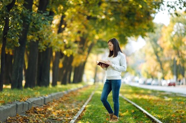 A bela feliz sorridente mulher de cabelos castanhos no suéter branco em pé com um livro vermelho nos trilhos do bonde no outono parque da cidade em um dia quente. folhas de outono dourado. conceito de leitura.