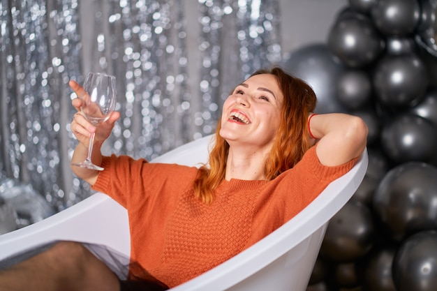 A bela garota ruiva alegra-se sentada vestida no banho. contra os balões de fundo