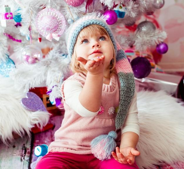 A bela garota sentada perto da árvore de natal