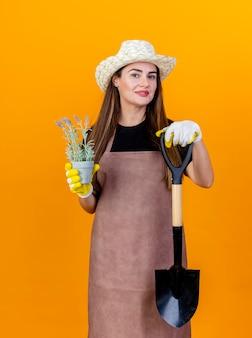 A bela jardineira sorridente usando uniforme e chapéu de jardinagem com luvas segurando uma pá com uma flor em um vaso de flores isolado em um fundo laranja