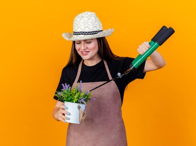 A bela jardineira sorridente usando uniforme e chapéu de jardinagem segurando e cortando uma flor em um vaso de flores com uma tesoura isolada em um fundo laranja