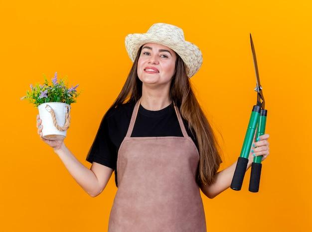 A bela jardineira sorridente, usando uniforme e chapéu de jardinagem, segurando uma flor em um vaso de flores com tesoura e espalhando as mãos isoladas em um fundo laranja