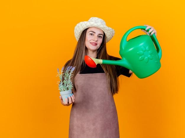 A bela jardineira sorridente, usando uniforme e chapéu de jardinagem, segurando uma flor em um vaso de flores e levantando um regador isolado em um fundo laranja