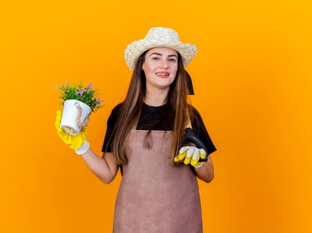 A bela jardineira sorridente, vestindo uniforme e chapéu de jardinagem com luvas, colocando a pá no ombro e segurando uma flor em um vaso isolado em um fundo laranja